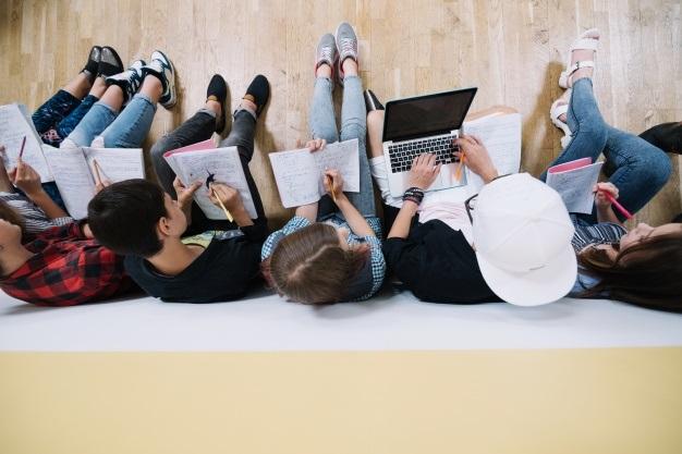 foto tirada de cima de cinco estudantes sentados no chão estudando juntos, com cadernos livros e um pc em cada mão
