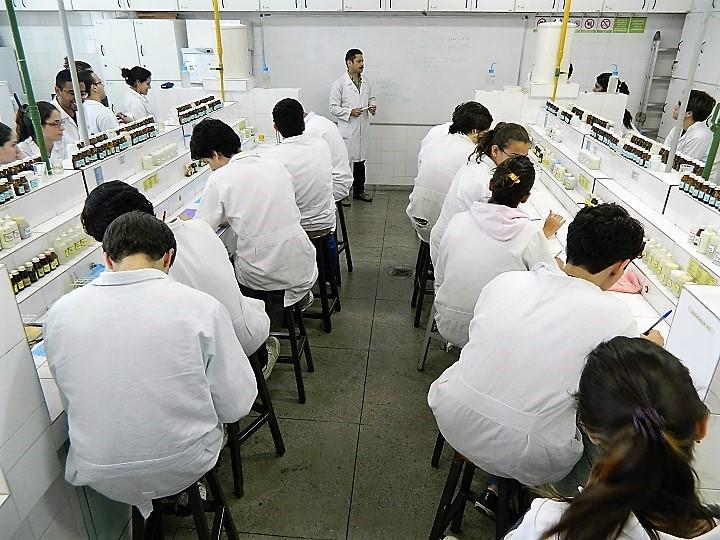 Alunos tendo aula em laboratório, cercados por vidros de itens químicos, com professor à frente da sala