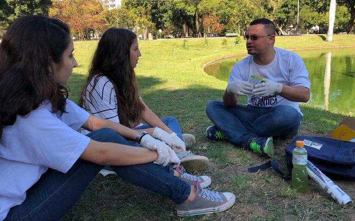estudante italiana sentada na grama conversando com outra aluna e o professor