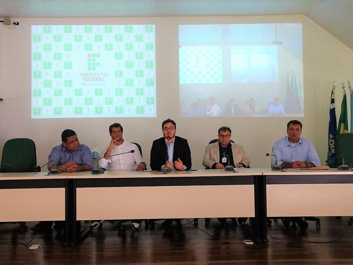 Participantes do evento à frente do auditório na mesa solene