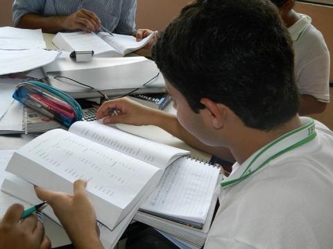 aluno, de perfil, lendo livro em sala de aula