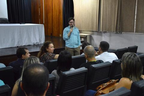 Rafael Almada fala ao microfone na frente do auditório cheio