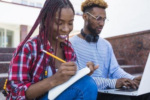 Uma moça negra escreve num caderno e um rapaz negro digita no laptop