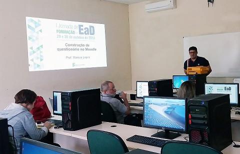 Professor à frente de uma sala cheia de computadores, com uma apresentação de slides ao fundo